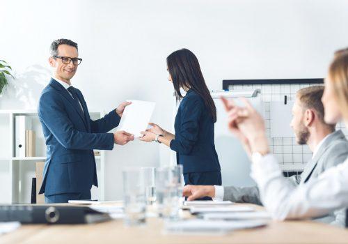 boss rewarding manageress at modern office