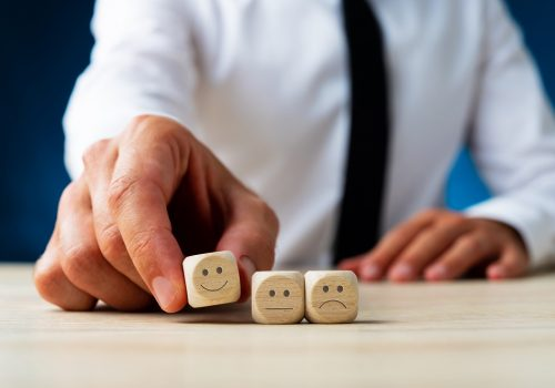 Closeup of a man choosing wooden dice with smiling face out of three options in a conceptual image of customer satisfaction.