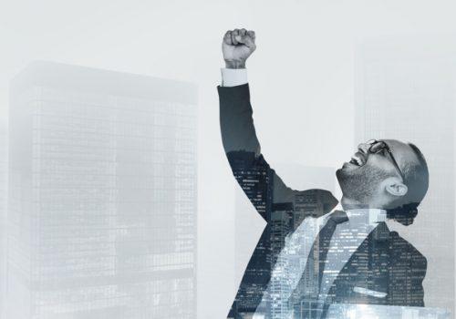 Successful businessman raising his hand in the air